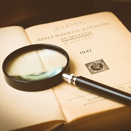 Image of a book with a magnifying glass on top of it.