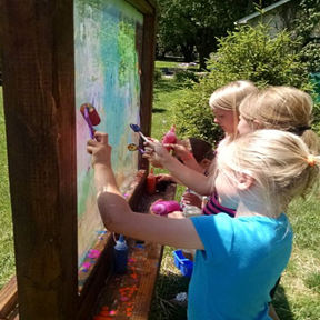 image of children painting outside