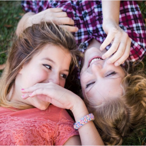 image of two teenage girls laying on grass