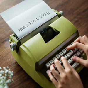 image of typewriter with hands typing the word marketing