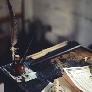 image of fountain pen and desk and papers and quill pen