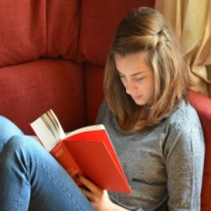 teen girl reading book in a chair
